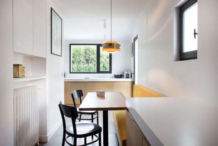 Tthe breakfast nook has the same custom oak and Corian cabinets as the kitchen, plus a wall cabinet for storing tea, coffee, and cereal. The back window overlooks the garden.