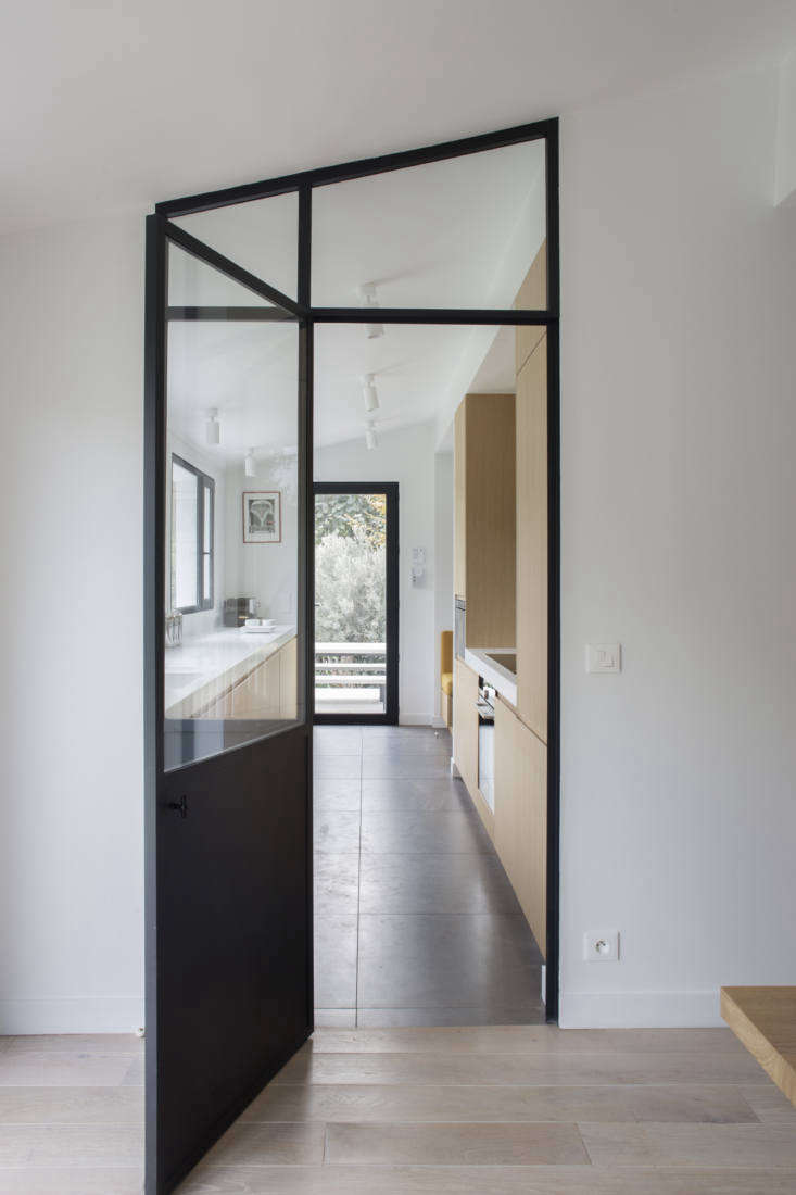 The steel door frame traces the shape of the eave. Note that the flooring shifts from porcelain tile to wide oak boards with a white oil finish. In the market? See our Guide to The Only 6 Wood Styles You Need to Know.