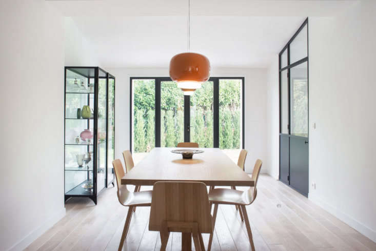 A new wall of steel-framed French doors brightens the space and opens it to the garden. The orange glass light is the Chouchin loading=