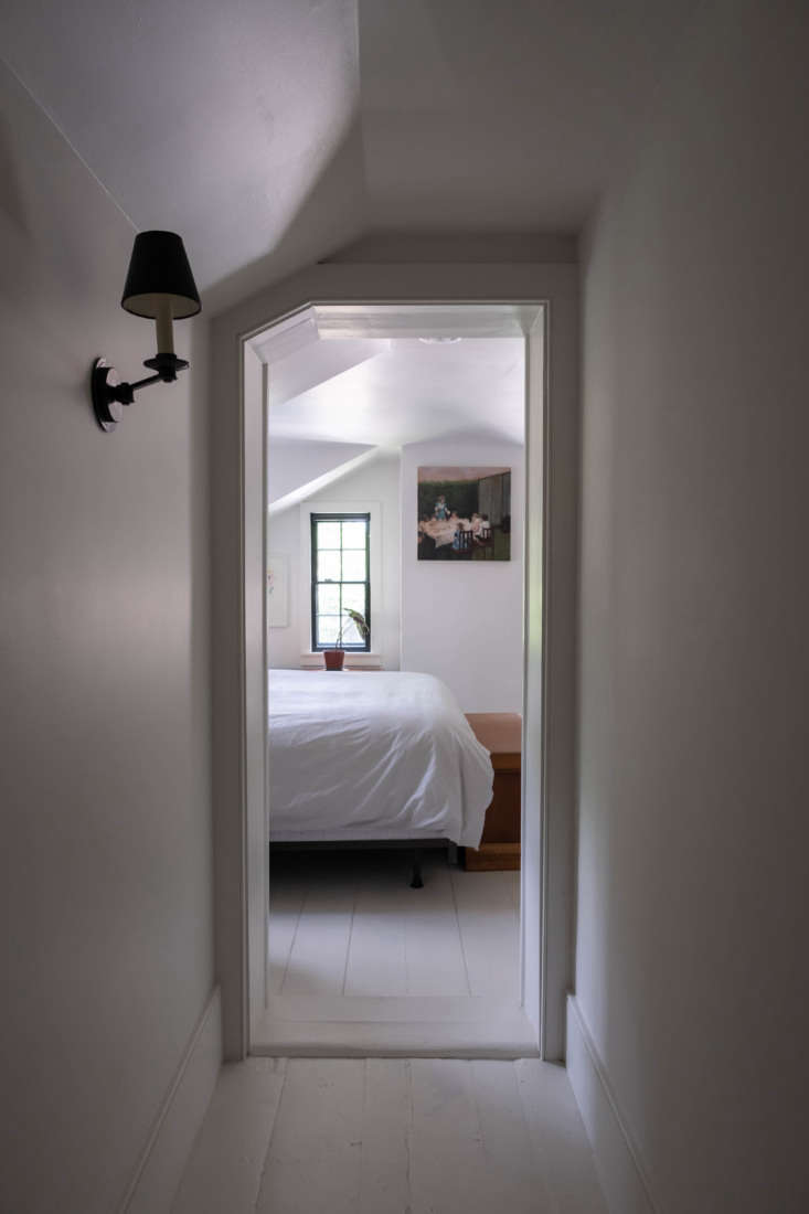 Upstairs, a narrow, white-painted hallway leads to one of the house's four bedrooms, which the couple uses for guests.