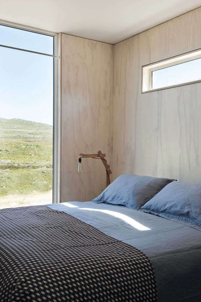 The master bedroom overlooks sweeping views of the nature reserve. The blue linen sheets and patterned cover are from Country Road (no longer available) and the bedside light is a vintage 50s Danish table lamp.
