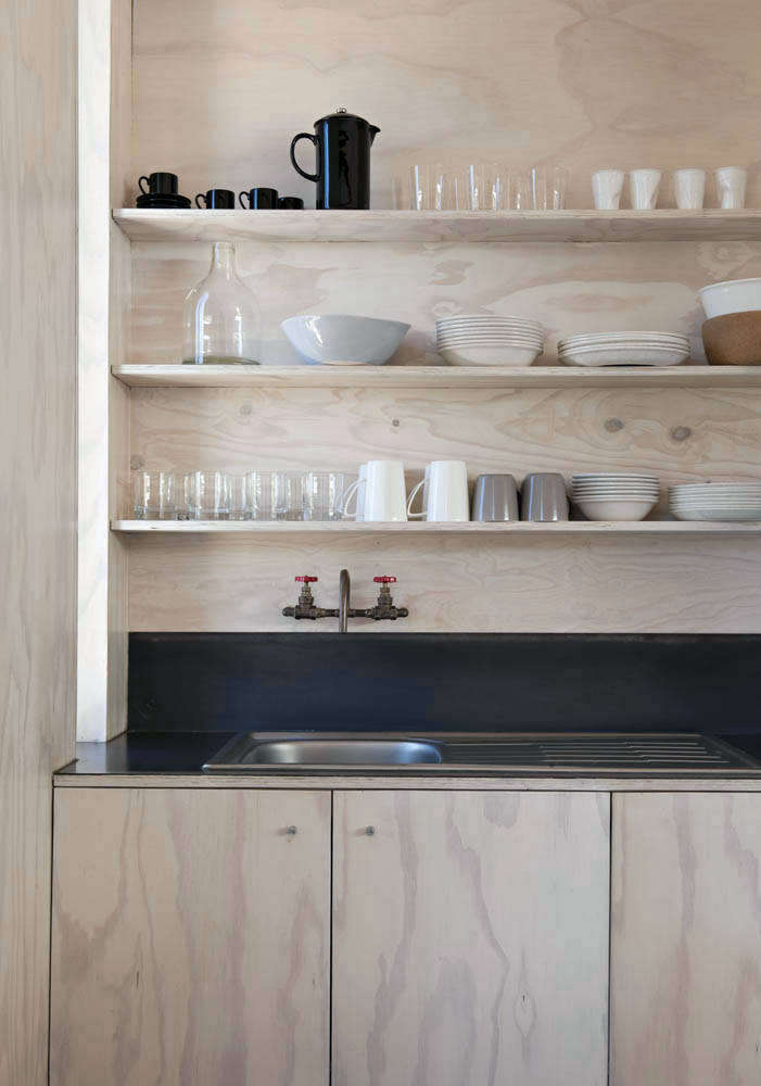 The architects enlisted a boat builder to work on the plywood joinery throughout the house, including the compact kitchen, which was designed on a budget and has countertops and a backsplash made of mild steel that was heated and hot waxed on-site. The kitchen faucet was also made on-site with plumbing parts.