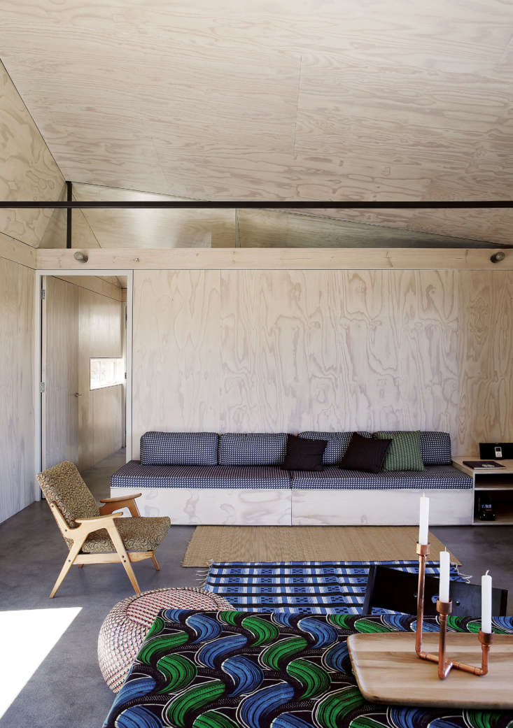 A built-in plywood bench upholstered with a checked fabric anchors the living space.