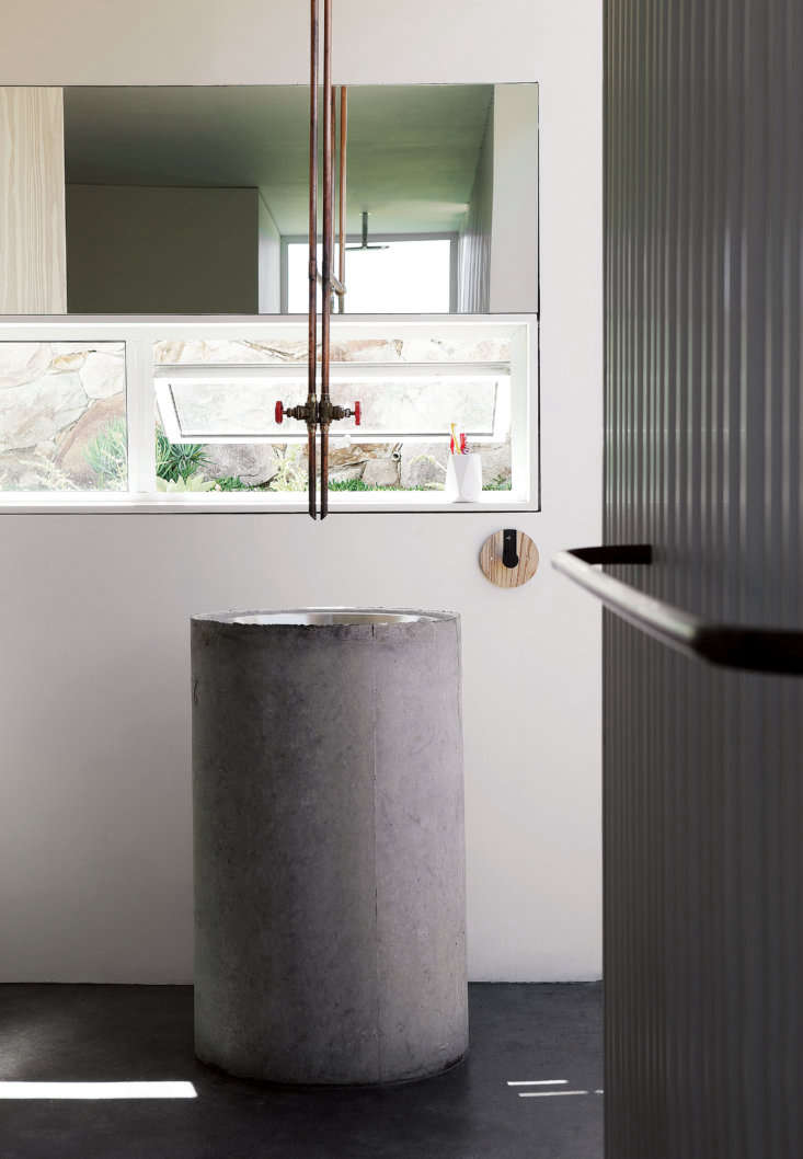 """The architects designed the communal """"bathhouse"""" with a large sink made of a stainless steel kitchen prep bowl set into a pre-cast concrete plumbing pipe. The faucet, like the one in the kitchen, is made from copper plumbing pipe."""