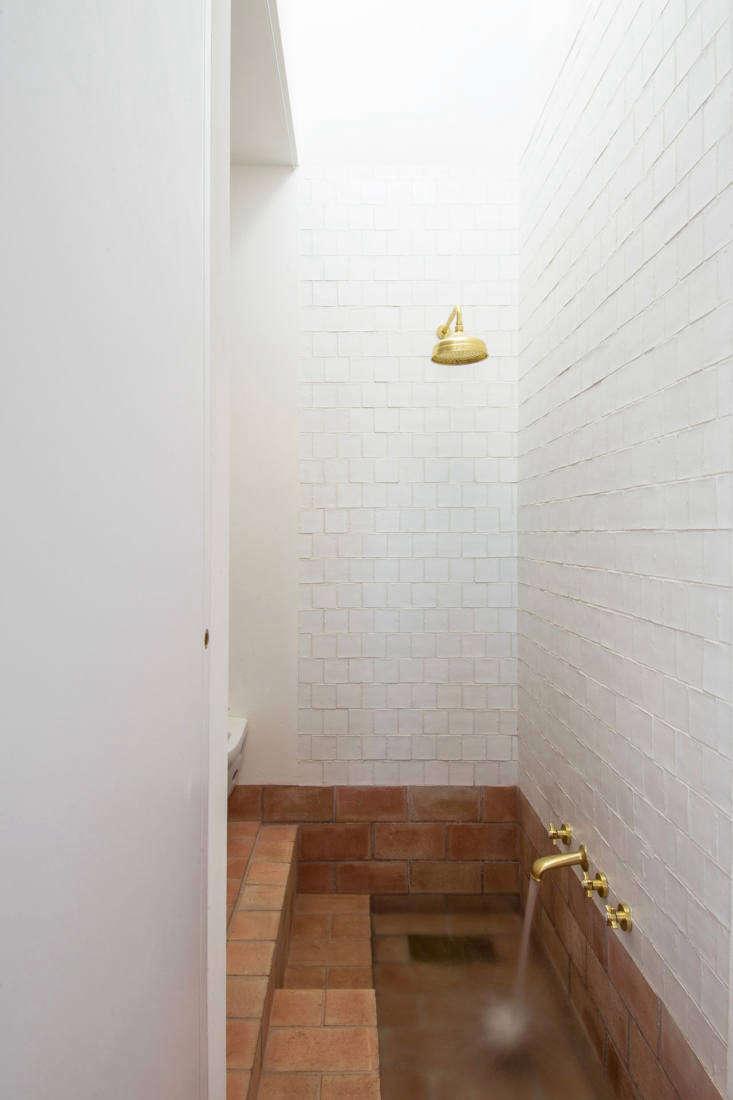 the shower is clad in handmade matte white porcelain tiles. the brass shower fi 23