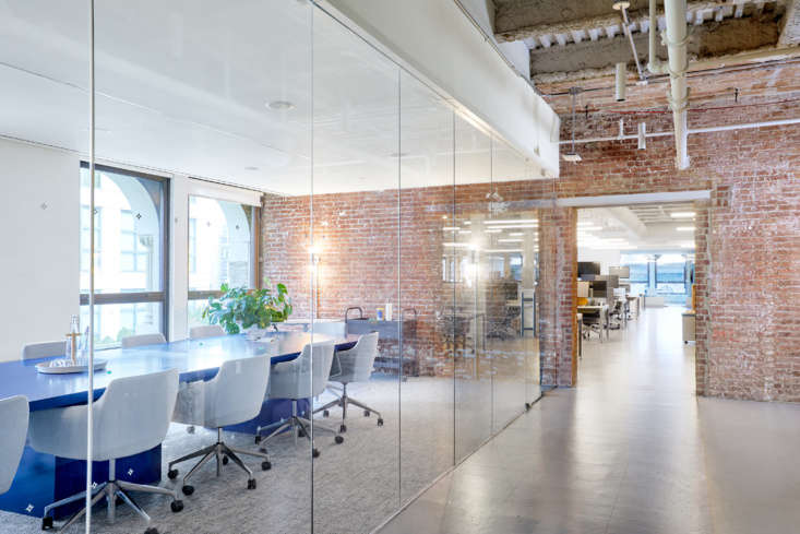 a glass walled conference room creates a private room for meetings but allows f 16