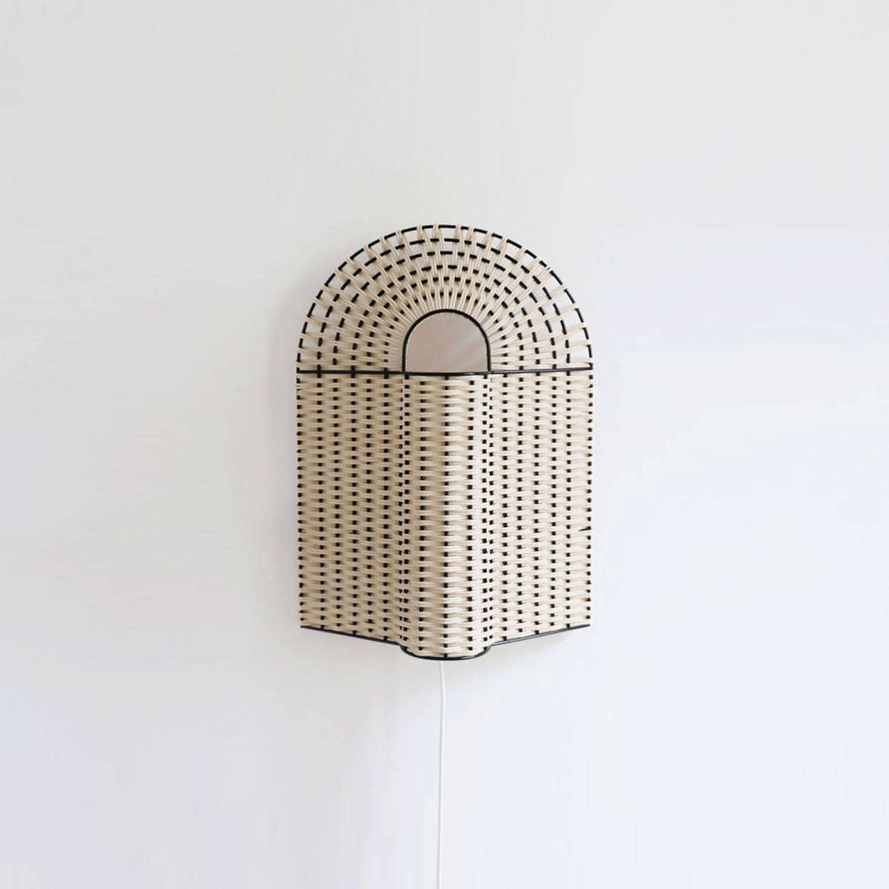 The Paon Medium Lamp in Natural Rattan with black lacquered metal is €335. The lamp can sit on a mantel or table, as shown, or comes with a metal hanging piece to mount on the wall.