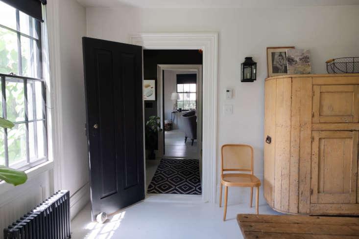the front door opens into a central stairway, painted dark, in benjamin moore&a 10
