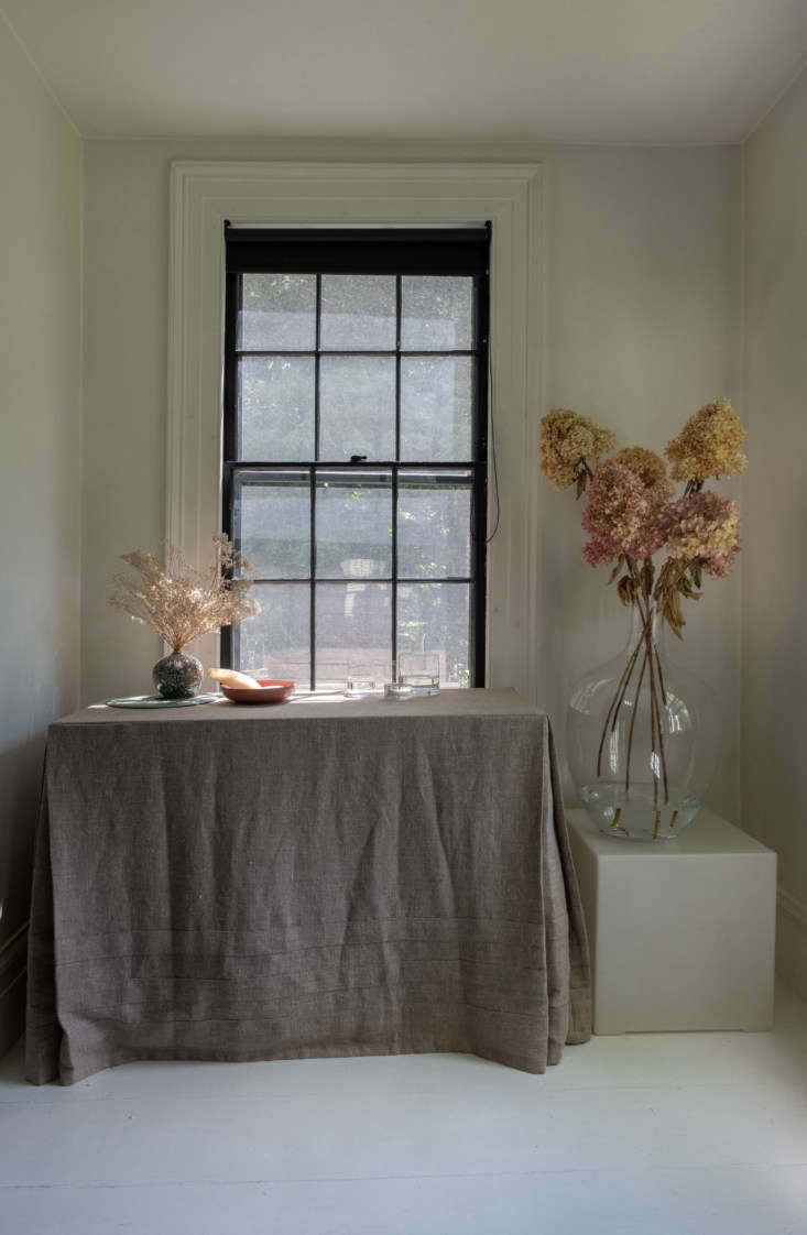 In the dining room, white walls contrast with the black trim on the paned windows. (&#8