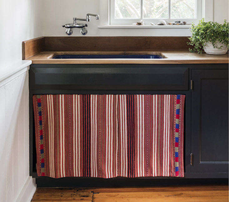 In her Bellport, NY, summer house, architect Elizabeth Roberts had a sink skirt sewn from a vintage Guatemalan textile in lieu of cabinet doors (see Elizabeth Roberts at Home: The Architect's Own Beach House). For more ideas, go to New Old Trend:  Fresh Examples of Sink Skirts and Cabinet Curtains on The Organized Home.