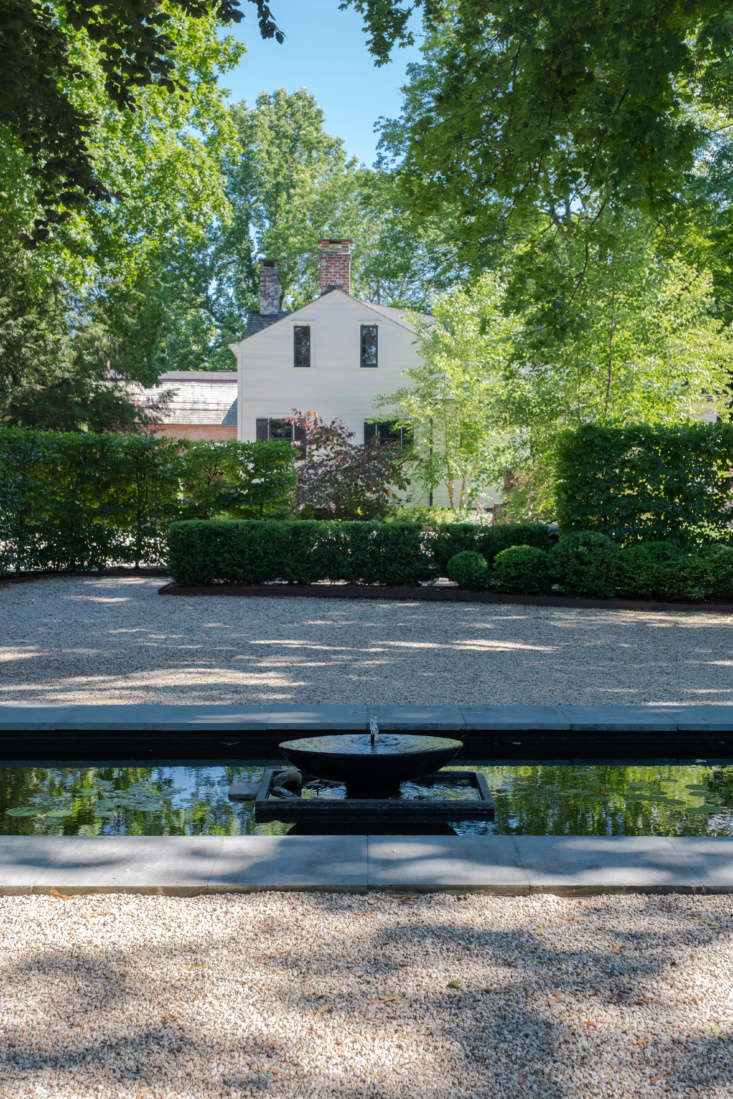 The back of the house—viewed from the steps of a small, screened outbuilding in the back garden, set for warm-weather dinners—with private gravel garden, reflecting pool, and flower gardens between.