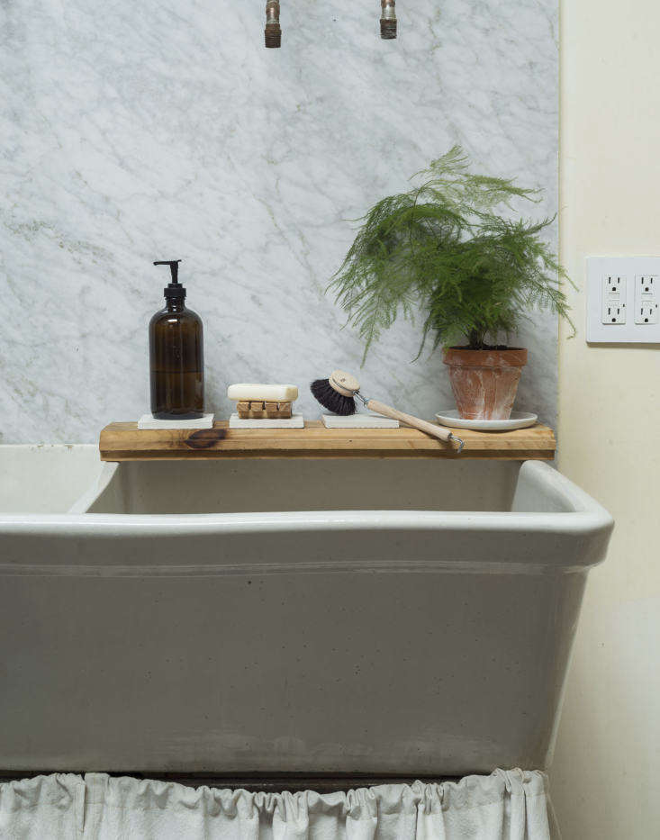 Below the short and long exposed-pipe faucets, a sink shelf is actually a length of leftover pine flooring, reused.