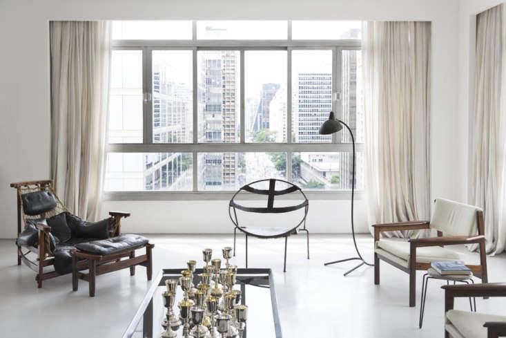 Hess utilizó agrupaciones de muebles del cliente para crear múltiples áreas de asientos y comedores.  Aquí, una colección de copas de vino plateadas en una mesa de café de vidrio está rodeada de sillas antiguas, incluida una silla Jean Gillon Jaganda de Brasil a la izquierda.