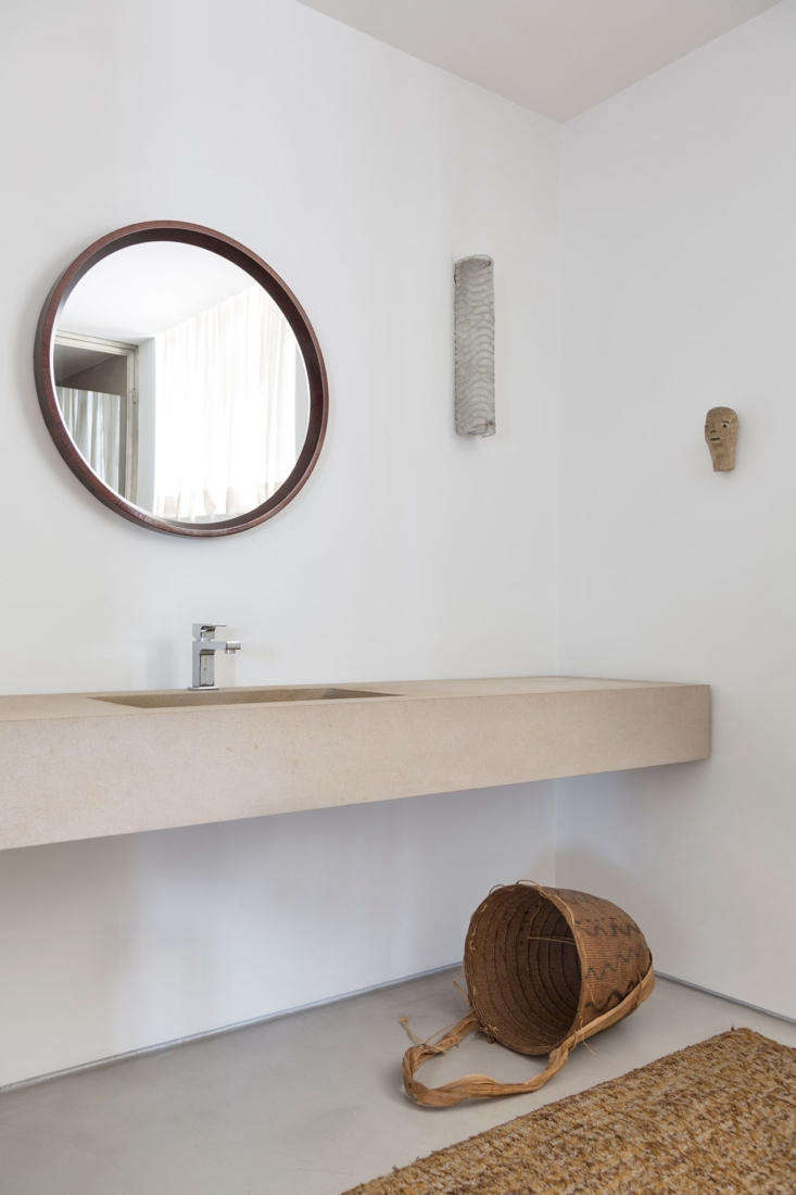 A floating concrete counter with a circular, wood-framed mirror in the bathroom off the primary bedroom.