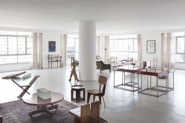 Otra vista de la sala de estar abierta.  Observe cómo Hess agrupó una colección de sillas escultóricas alrededor de una mesa de café y usó una alfombra para anclar el área de asientos.