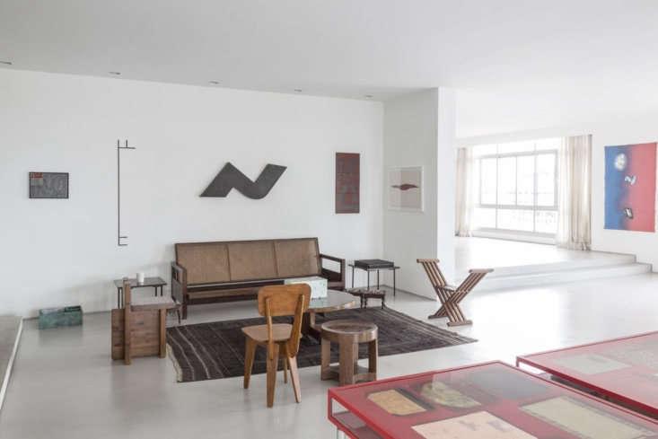 Un banco de ratán tejido antiguo se enfrenta a un grupo de sillas.  En el extremo izquierdo hay una silla de pino diseñada por la arquitecta Lina Bo Bardi en la década de 1950, y en el extremo derecho una silla plegable con estructura en X de mediados de siglo.