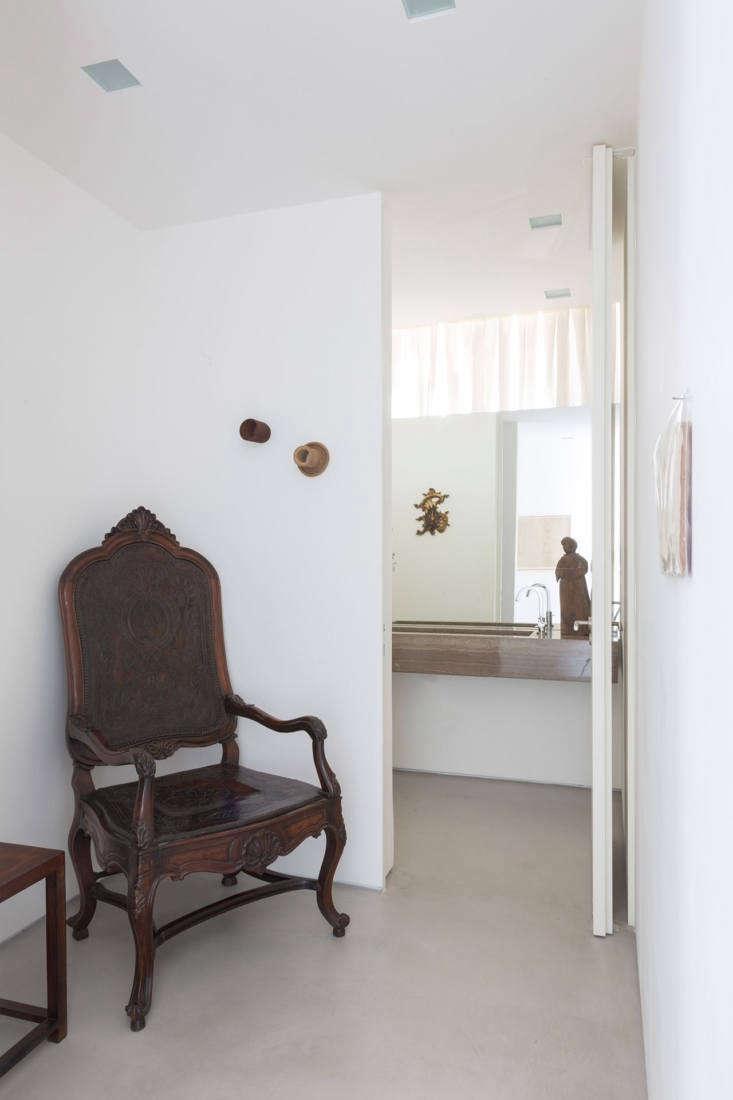 Una silla antigua a la entrada de un baño de visitas moderno.