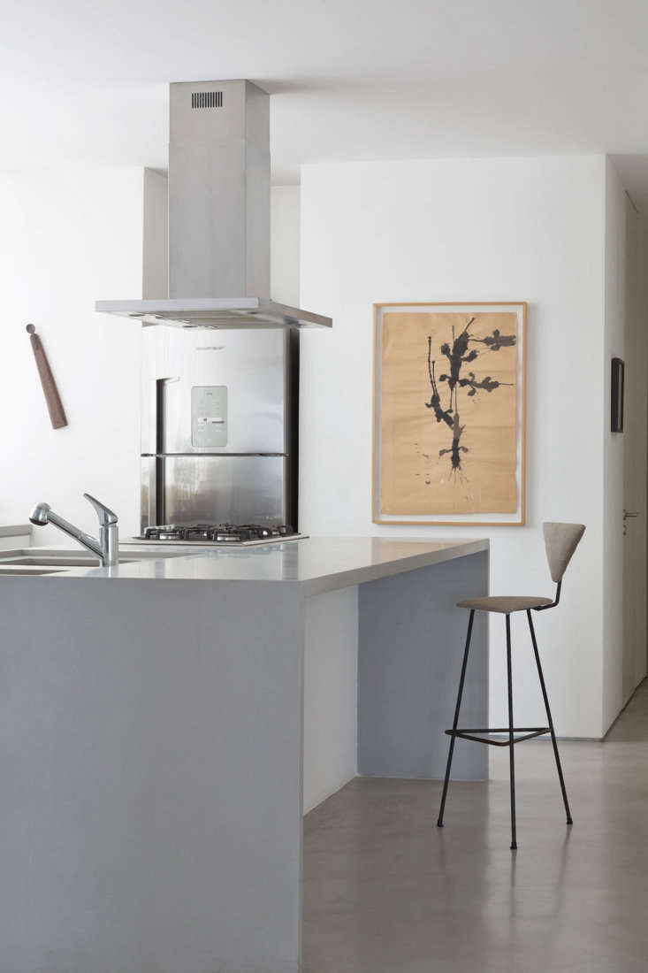 A modern kitchen with a concrete waterfall kitchen island and minimalist white cabinets.