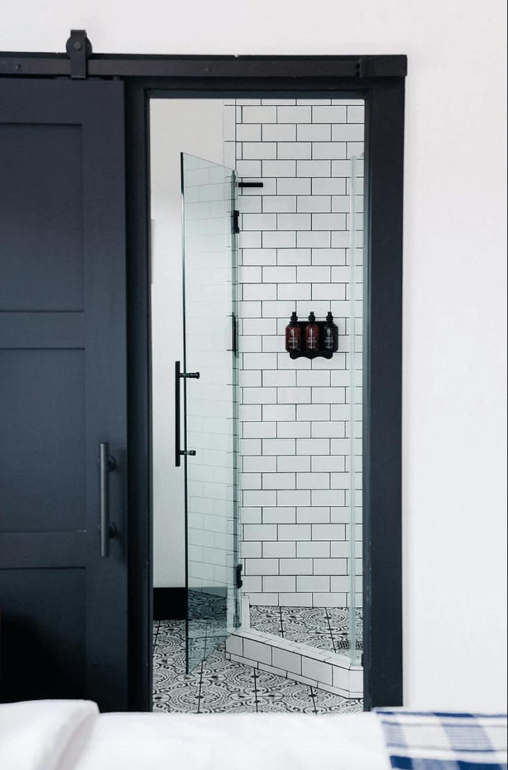 a guest bath behind a sliding black barn door. 17