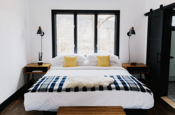 Guest rooms have a sophisticated-camp vibe: Beds are made with Frette linens and plaid wool throws from Faribault Woolen Mill Co.