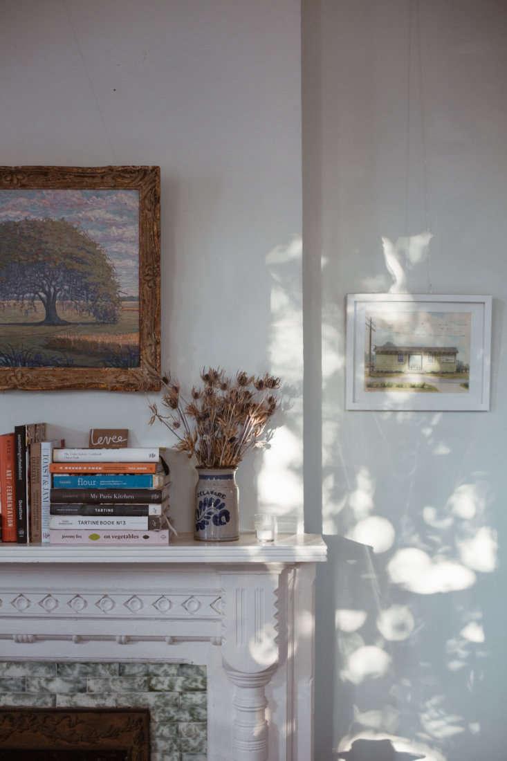 Many New Orleans homes have original fireplaces that are no longer working; on the Levee mantel in the back room, Balzebre has her in-house cookbook collection.