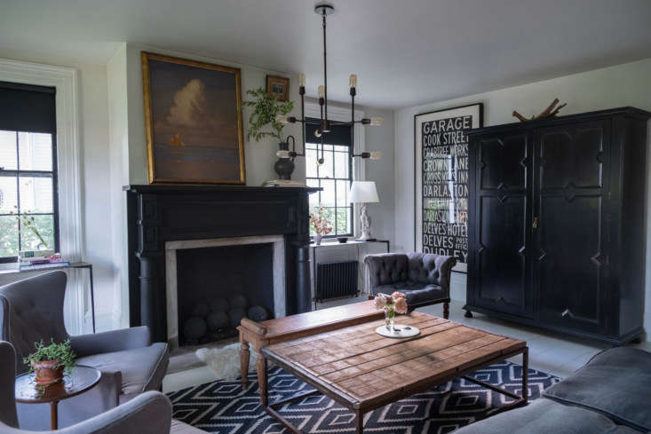 Across the entryway is the living room, with an eclectic mix: sheepskin, a light fixture from Restoration Hardware, side-by-side coffee tables, and twin stone lamps in the shape of eagles that were acquired with the house. The posters at the far end of the room are vintage, from British train stations.