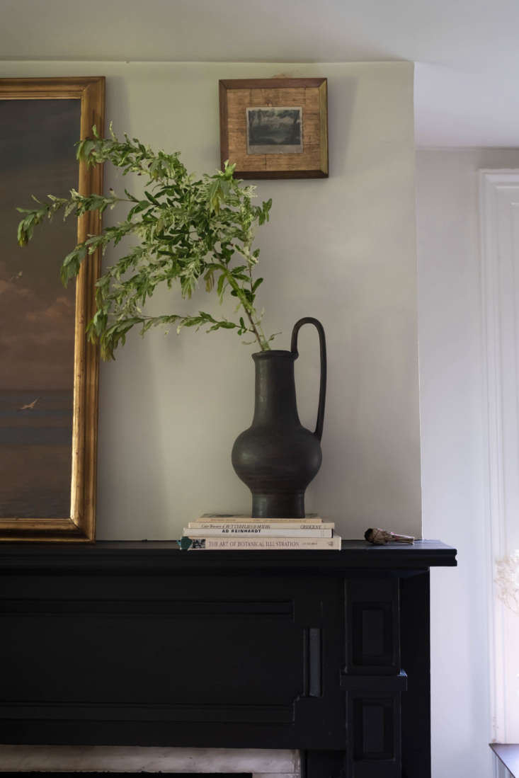 Above the mantel, a small painting hung unexpectedly high creates a vignette with a tall vase, an anniversary gift.