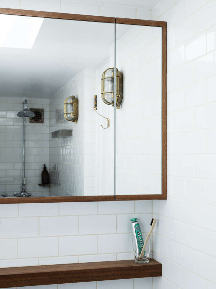 the tiny shower—the apex of the triangular floor plan—is reflected in the m 18