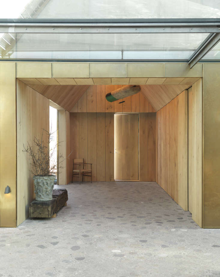 The entrance to the restaurant is paneled in Dinesen Oak Natural with a brass accent wall. The custom terrazzo floor is made of large river stones, which, the designers say, can be felt when walking on the floor with bare feet.