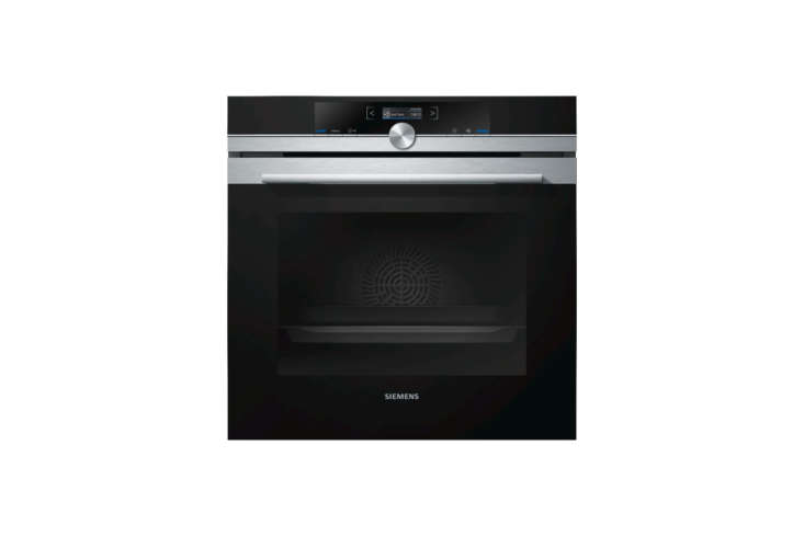 Most of the appliances are integrated into the green-painted MDF cabinets—all are from Siemens. Shown here are two Siemens Built-In Single Ovens for £699 each at John Lewis.