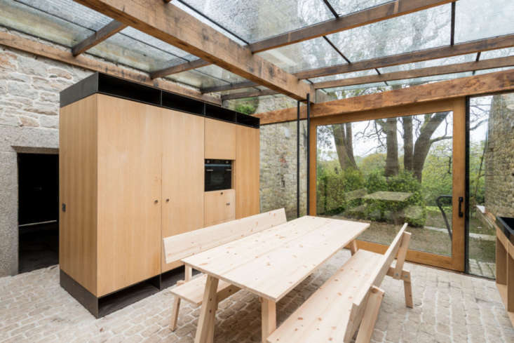 The roof and one entire wall of the addition is glass. The picnic table and benches are from Piet Hein Eek&#8\2\17;s Industriell collection for Ikea.