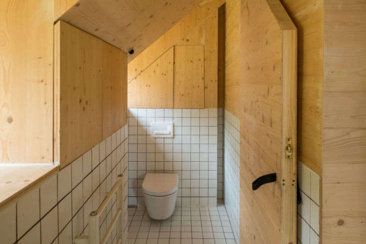 White square tiles with black grout in the upstairs bath echo the bathrooms in the main house. Like the wall-mounted toilet? Check out\10 Easy Pieces: Wall-Mounted Toilets.