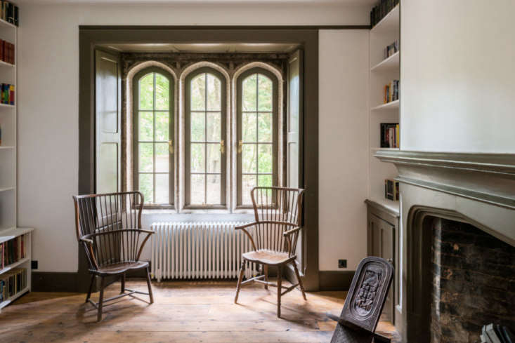 Olive-green trim is featured in each room. Here, in the library, minimalist bookshelves have been seamlessly built in alongside existing millwork.