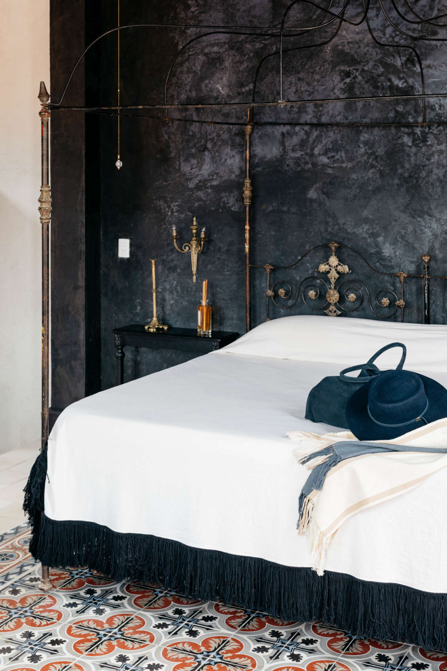 Guest rooms are fitted with vintage pieces, iron bed frames, and plenty of candles.