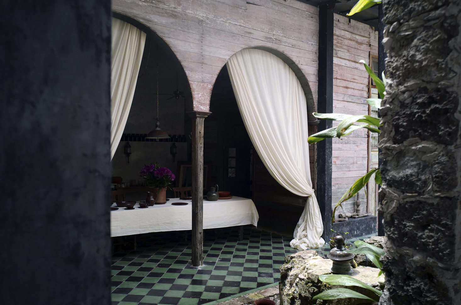The tiled veranda, with long, sultry curtains.