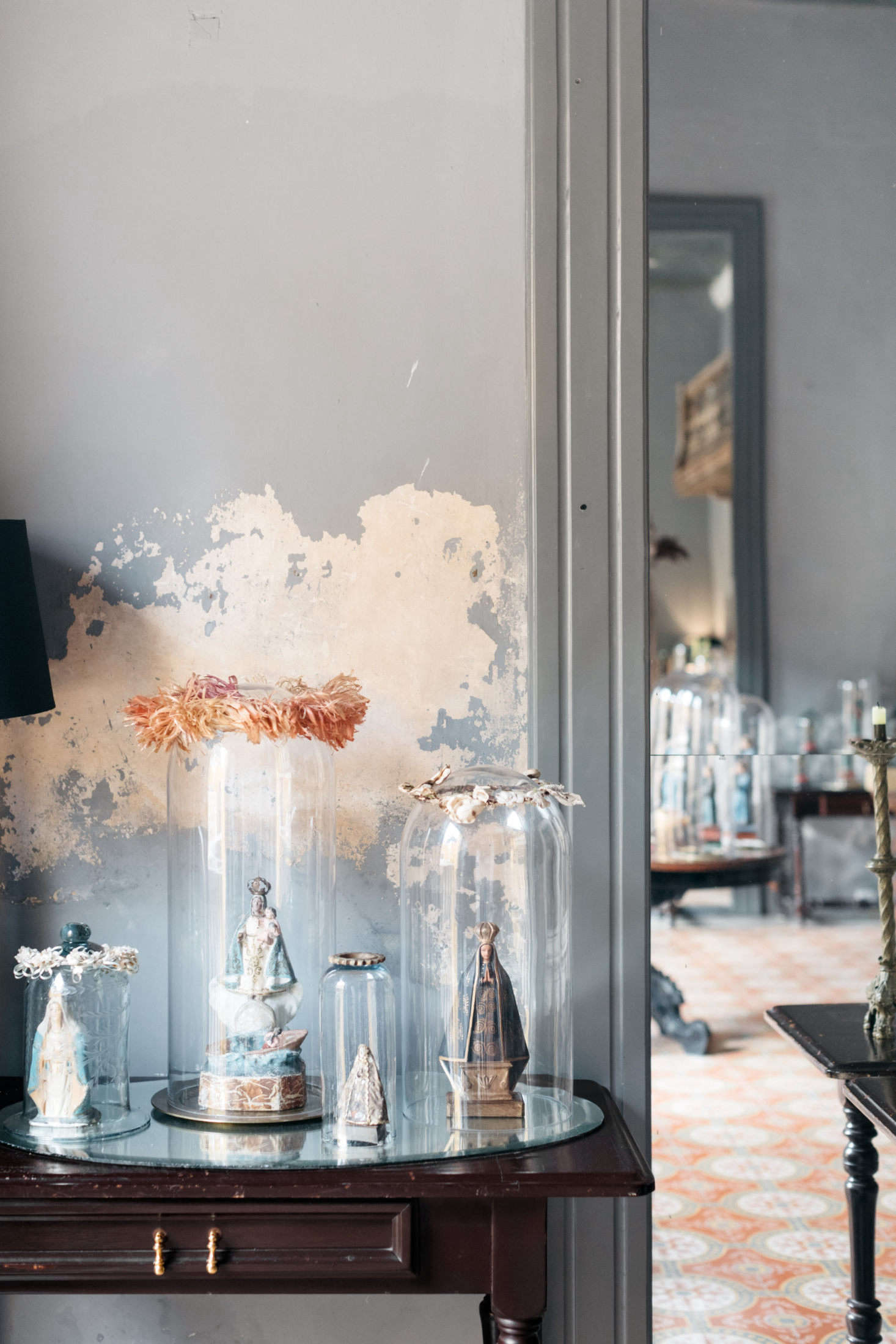 Antique figurines of saints and virgins are enshrined in glass, a nod to the city&#8