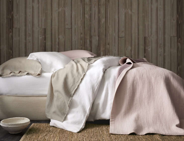 a neutral bed made with eileen fisher washed linen bedding in pure white and pe 11