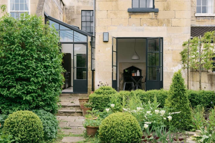 the house is part of a series of connected cottages. steel framed french doors  18