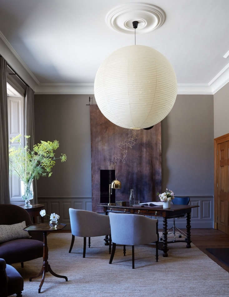 The study, featuring a handwoven tapestry by Lucy Bathhurst of Nest Design, a Kaarlo Bergbom brass desk lamp, and an antique partners desk. Thetapestry was designed in response to the colors and materials found within the room, and the gold line traces the edge of the woodlands through the estate.