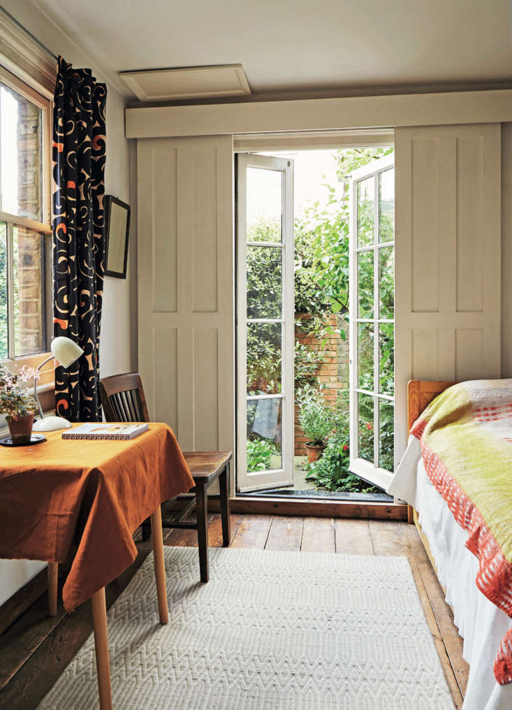 A dreamy guest room occupies the back extension on the ground floor. The French doors (with original sliding shutters) open to the upper level of the garden. Baldwin found the Marimekko curtain fabric at Portobello Market; the coverlet is from India.