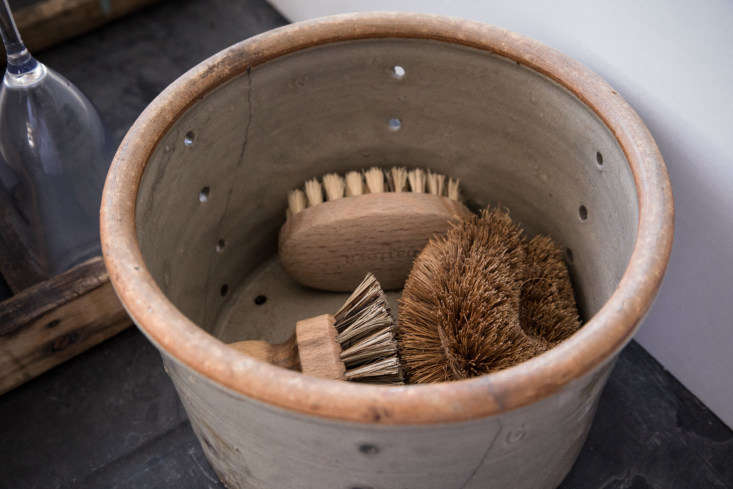 Next to the sink, a vintage pot houses scrubbing brushes.