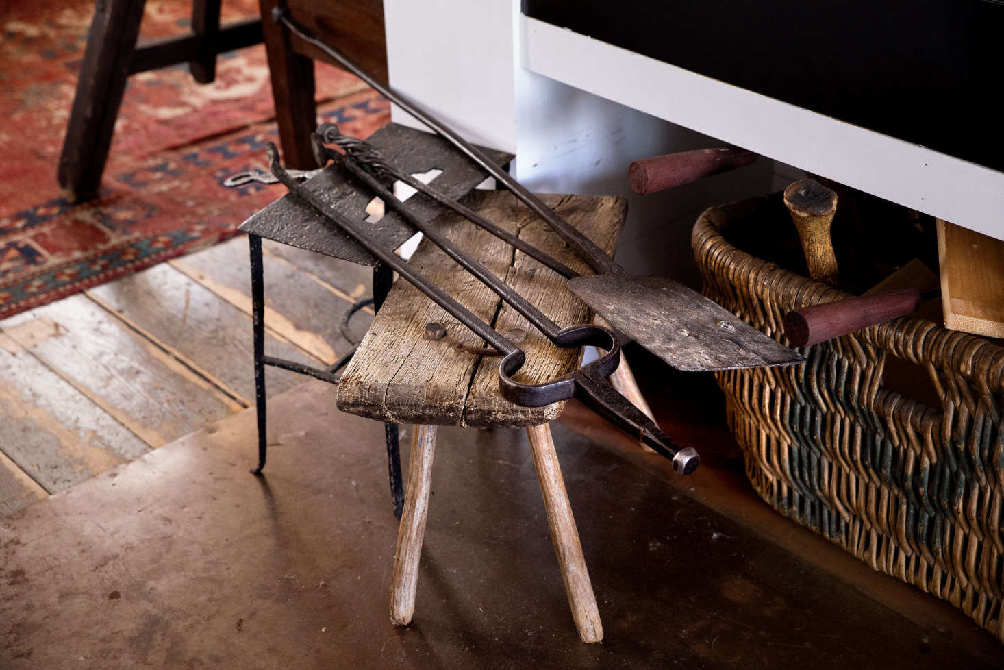 American fireplace tools from the 00s rest on iron standing trivet and an antique stool from Tuscany.