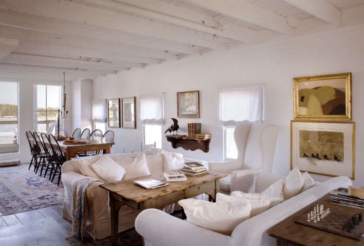 White linen-covered furniture and gold accents give the living room a cozy feel. The top painting on the far right is by an Irish artist, living in Maine. Below is a painting found in France at an antique fair.