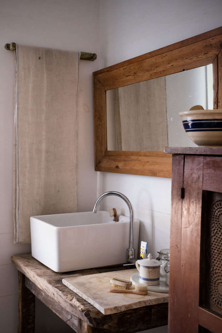 In the master bath, a Tuscan stand made from old farm boards supports a ceramic sink found at Baileys Home and Garden in England. The mirror is a striped, early pine ogee frame, circa 90.