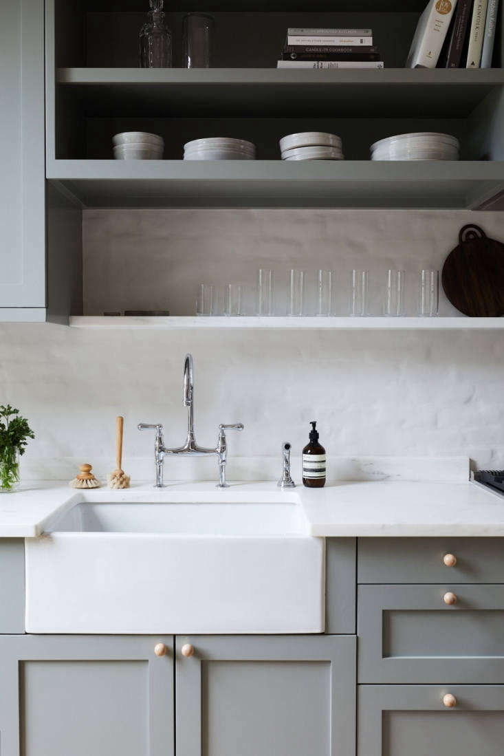 The owners and their team chose a farmhouse sink and chrome bridge faucet for a classic look they would never tire of.Photograph by Nicole Franzen fromRehab Diary: Monochromatic Luxe in Park Slope.