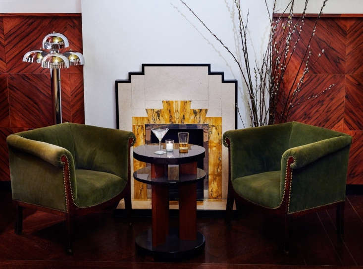 Olive green velvet club chairs—vintage—and a fireplace with marble inlay. The walls are clad with Tineo, a wood typically used for drum kits.