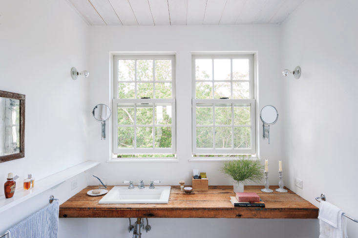 In architect Sheila Narusawa's own Cape Cod home, a simple bathroom counter is neatly fitted with the essentials (scrub brushes, soap dishes), plus a few nice-to-haves (twin candlesticks, books, and bottles of perfume).