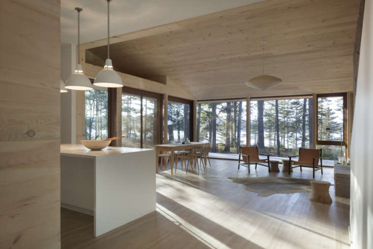 the front door opens to a wood paneled gathering space with a kitchen at one en 11