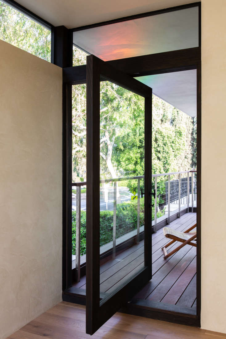 on the second floor, a wood framed pivot door opens to the front balcony. photo 21