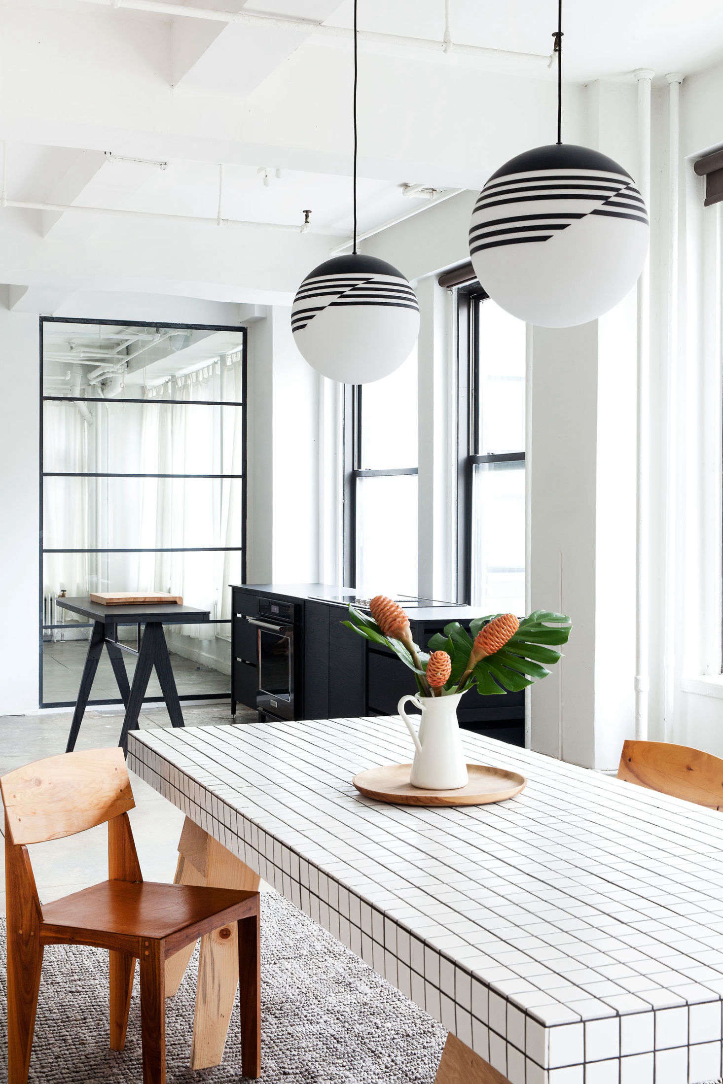 The duo-tone tiled table was a DIY affair. (Interested in trying your hand at something similar? SeeDIY: A Summery Side Table by Two Young Paris Architectsfor step-by-step instructions.) The Optical Pendant Lights are from Lee Broom.